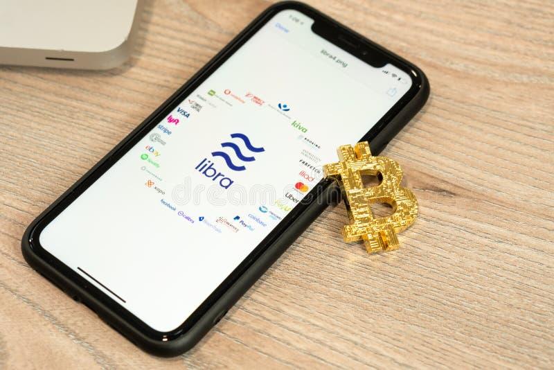 18. Juni 2019 Ljubljana Slowenien - Smartphone mit Waagelogo und seine Partner auf ihm, nahe bei Bitcoin-Münze Facebooks stockbild