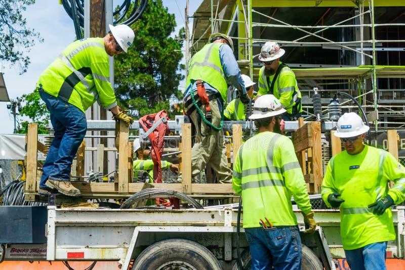 Juni 24, 2019 Mountain View/CA/de V.S. - Team van bouwvakkers die heldere gele vesten en bouwvakkers dragen stock foto