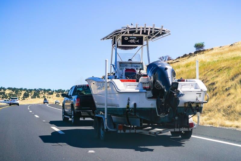 26 juni, 2019 Oakdale/CA/de V.S. - Vrachtwagen die een boot op de snelweg slepen royalty-vrije stock afbeelding