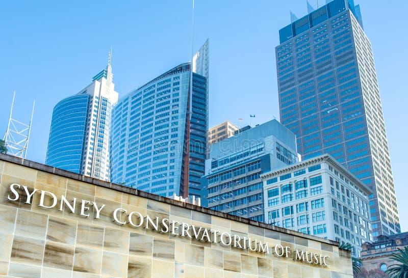 Juni 30 2017 - Sydney, Australien: Tecken för conservatoriumen av musik och stadsbyggnader royaltyfri fotografi