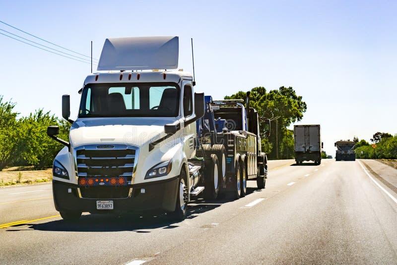 26 juni, 2019 Tracy/CA/de V.S. - Vrachtwagen die een andere vrachtwagen slepen stock foto's