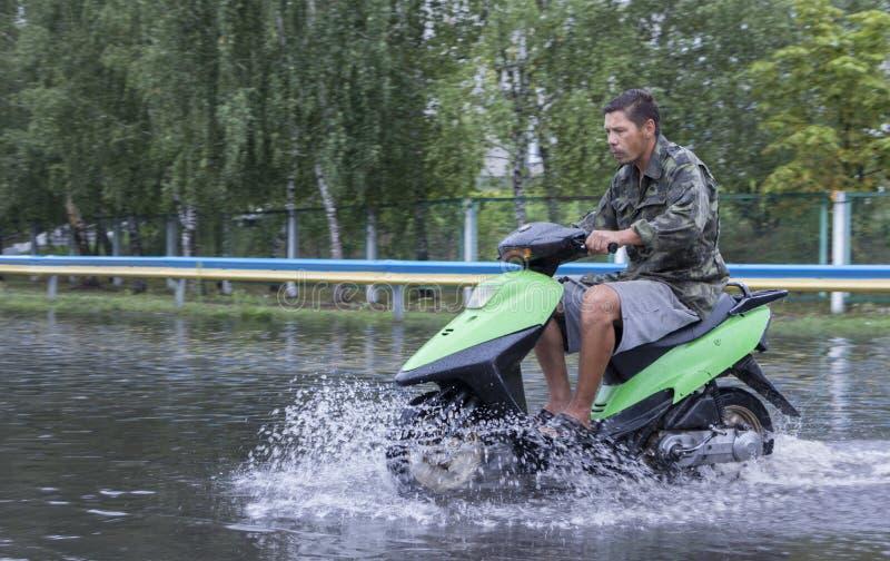 Juni 21, Vyshenky Ukraina Följder av duschen En motorcyklist rider längs en översvämmad gata arkivbild