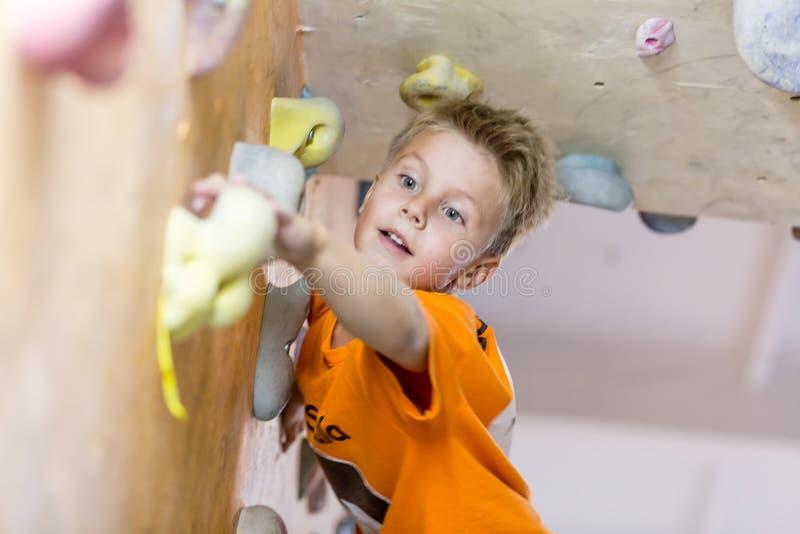 Junior Climber som får hållen på klättringväggen royaltyfri foto