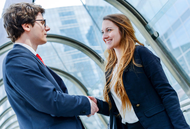 Junior executives dynamics shaking hands stock photography