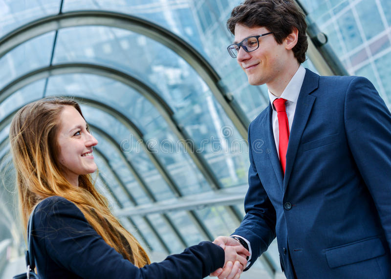 Junior executives dynamics shaking hands royalty free stock photography