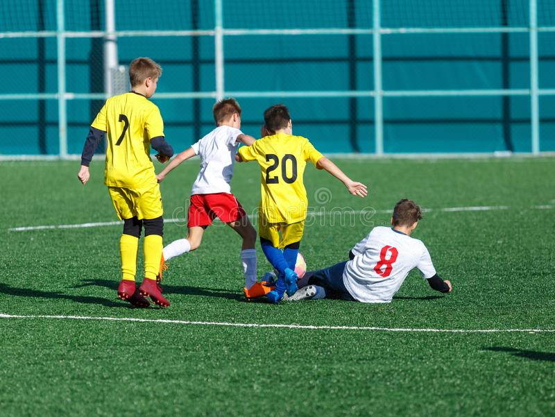 Junior football match. Soccer game for youth players. Boys in blue and white uniform playing soccer match. Football stadium stock photo