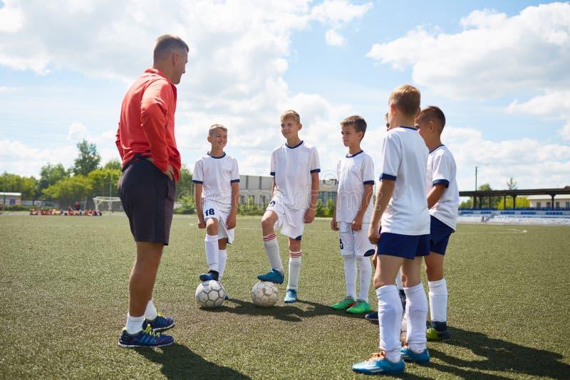 Junior Football Team Listening a entrenar foto de archivo