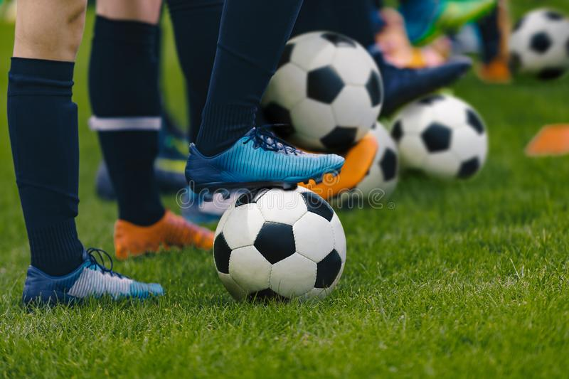 Junior Football Training Session. Players Standing in a Row with Classic Black and White Balls. Youths Practice on Soccer Field. Low Angle Close-up Image of stock image