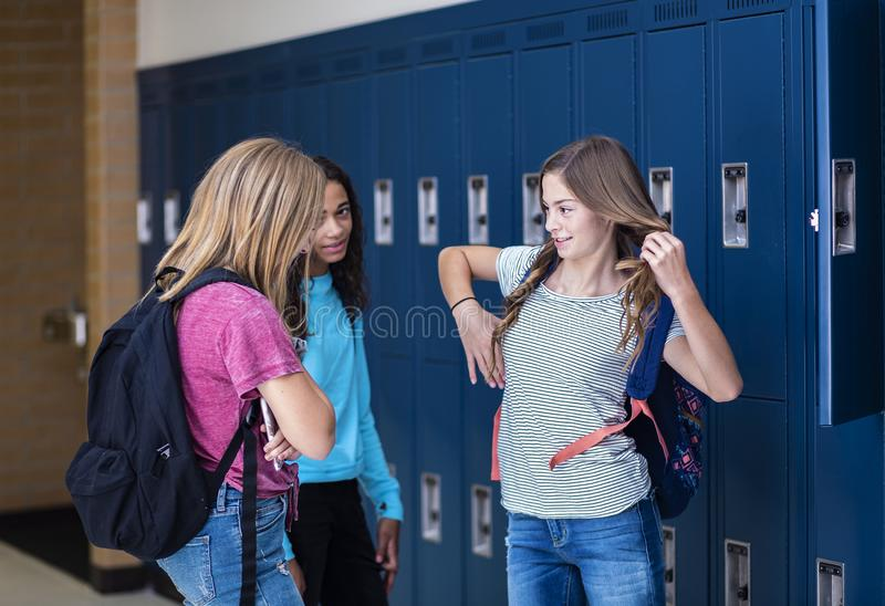 Junior High school Students talking and standing by their locker in a school hallway. Candid photo of Three Junior High school Students talking together in a royalty free stock photography
