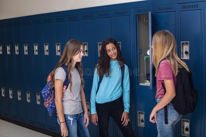 Junior High school Students talking and standing by their locker in a school hallway. Candid photo of Three Junior High school Students talking together in a stock photography