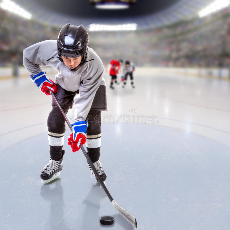 Junior Hockey Player Puck Handling in Arena. Boy hockey player handling puck on ice with arena full of fans in the stands and copy space. 3D rendering of hockey royalty free stock images