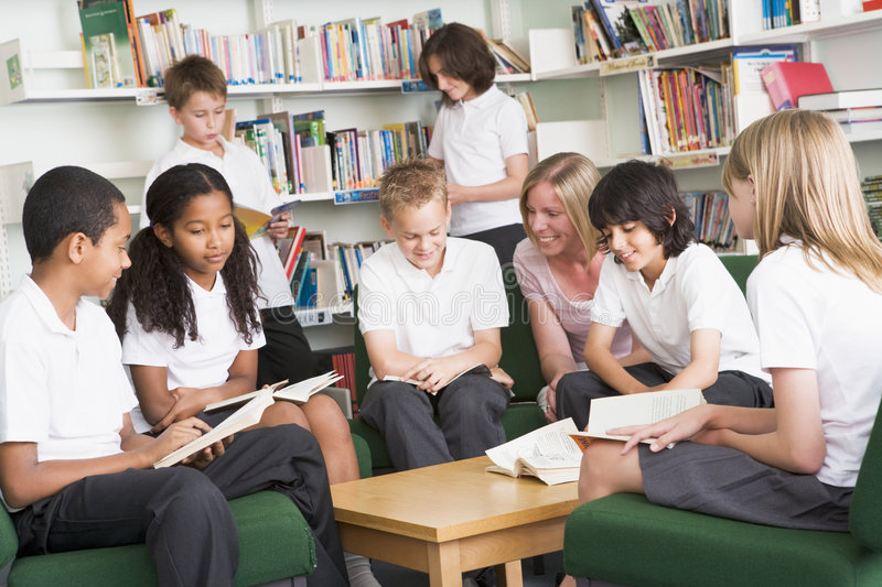 Junior school students working in a library royalty free stock photo