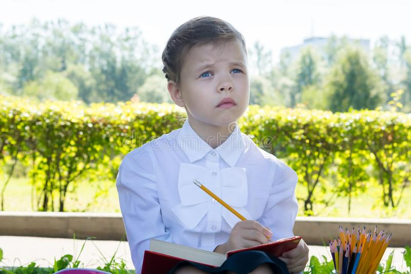 Junior schoolgirl wondered how to spell the word, doing homework in the fresh air in the park royalty free stock photography