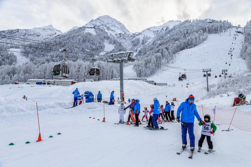 Junior ski downhill competition is held annually on snowy slopes of Gorky Gorod winter mountain ski resort. Children skiers queue stock images