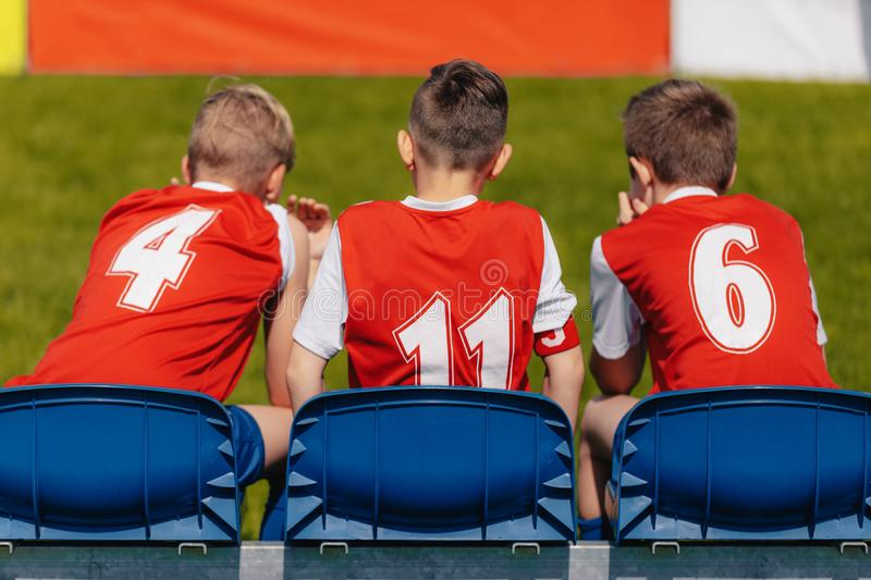 Junior Soccer Players Sitting on Football Soccer Team Bench royalty free stock photo
