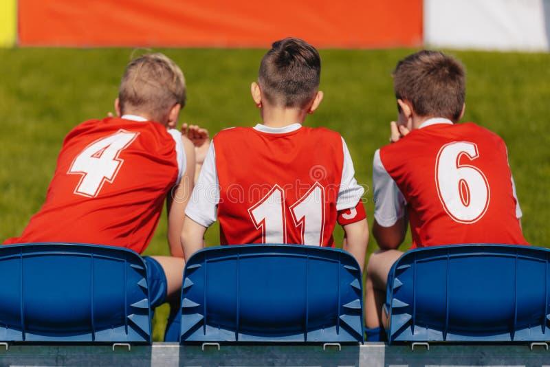 Junior Soccer Players Sitting på fotbollfotboll Team Bench royaltyfri foto