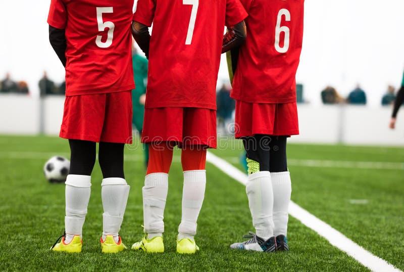 Junior Soccer Players Standing em uma parede Situação livre do pontapé durante o fósforo de futebol imagem de stock royalty free