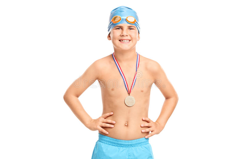Junior swimming champion in blue swim trunks. Junior swimming champion with blue swim cap and swim trunks looking at the camera isolated on white background stock image