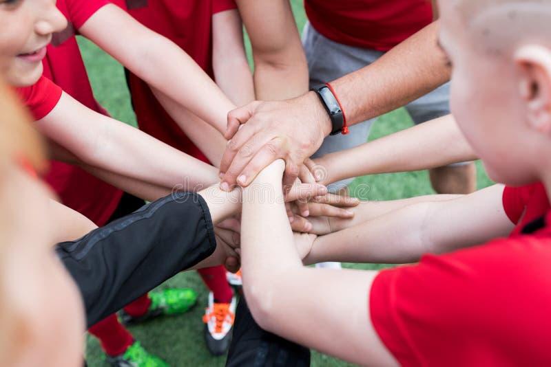 Junior Team Joining händer royaltyfri foto