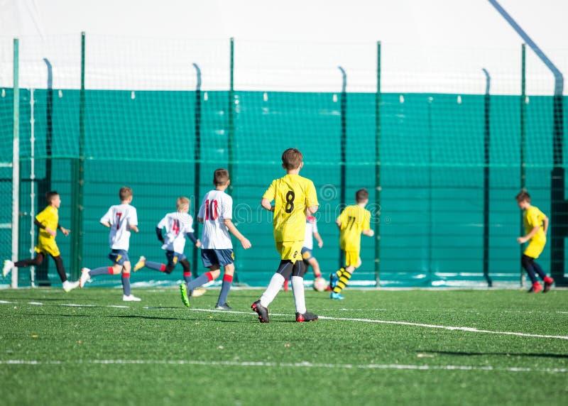Juniorfußballspiel Fußball-Spiel für Jugend-Spieler Jungen im Schrei und in weißer Uniform, die Fußballspiel spielen Fußballstadi stockfotografie