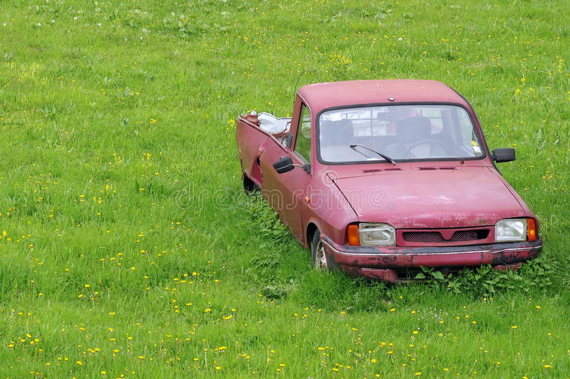 Junk car abandoned on a meadow stock images