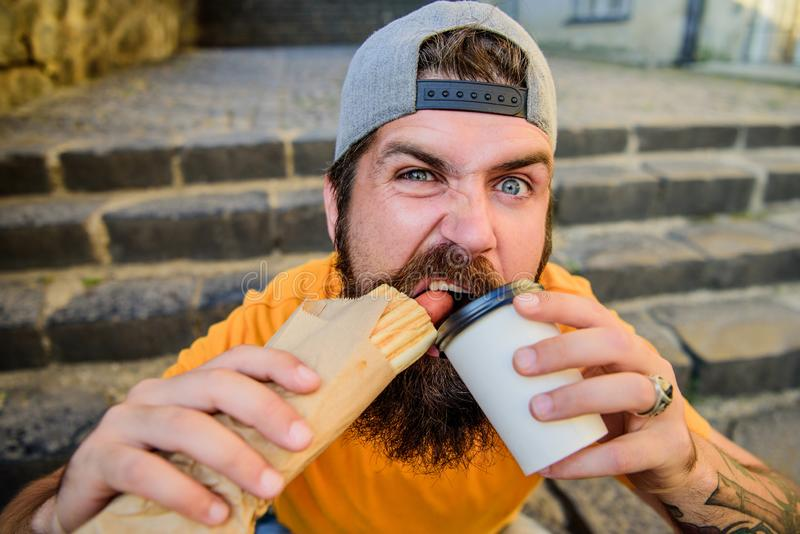 Junk food. Carefree hipster eat junk food while sit stairs. Snack for good mood. Guy eating hot dog. Street food concept. Carefree hipster eat junk food while royalty free stock photos
