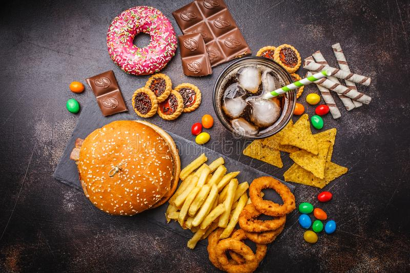 Junk food concept. Unhealthy food background. Fast food and sugar. Burger, sweets, chips, chocolate, donuts, soda, top view royalty free stock photography