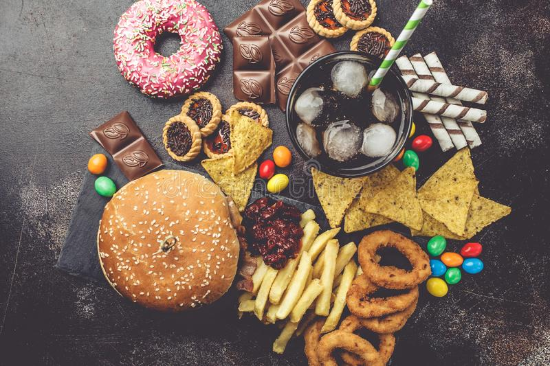 Junk food concept. Unhealthy food background. Fast food and sugar. Burger, sweets, chips, chocolate, donuts, soda, top view stock photo