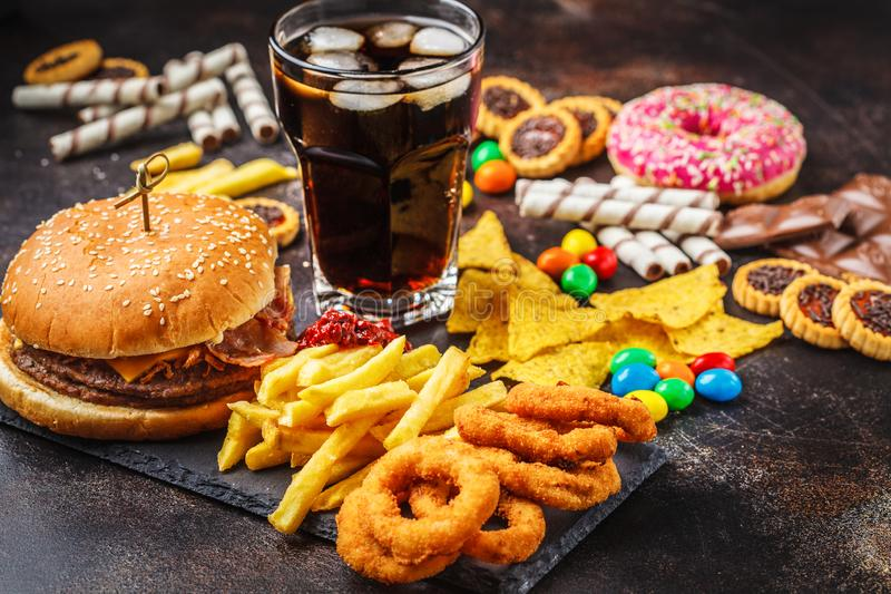 Junk food concept. Unhealthy food background. Fast food and sugar. Burger, sweets, chips, chocolate, donuts, soda royalty free stock image