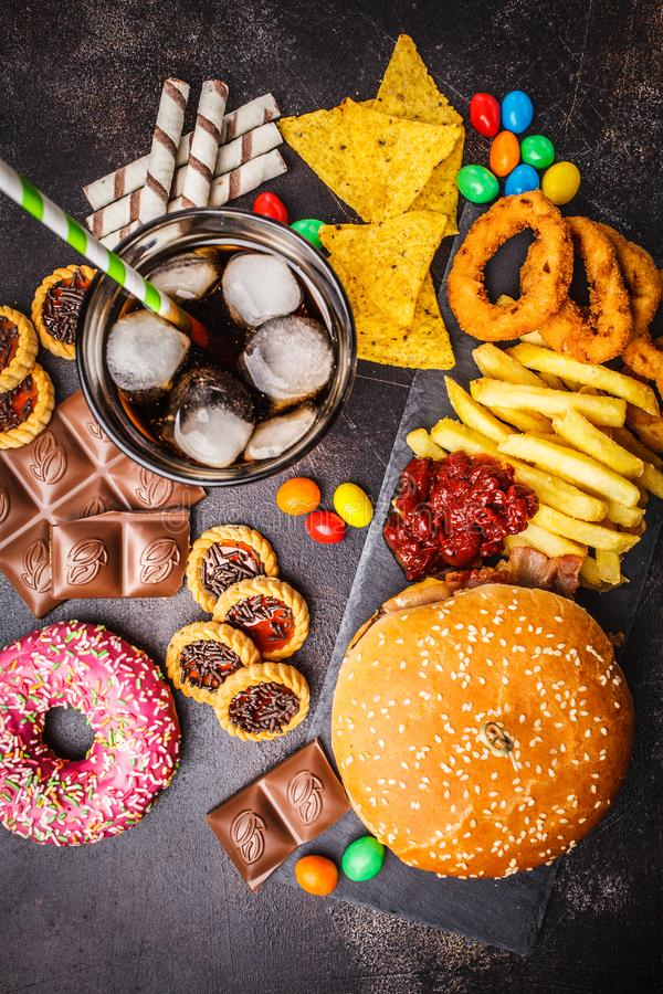 Junk food concept. Unhealthy food background. Fast food and sugar. Burger, sweets, chips, chocolate, donuts, soda, top view stock photos