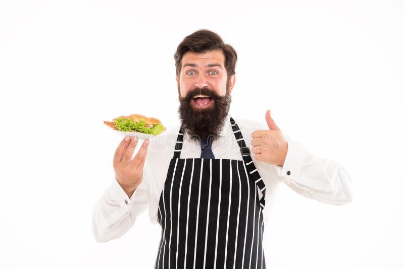 Junk Food Croissant delicioso El delantal barbudo del desgaste del camarero del hombre lleva la placa con la comida Concepto del  imagen de archivo libre de regalías