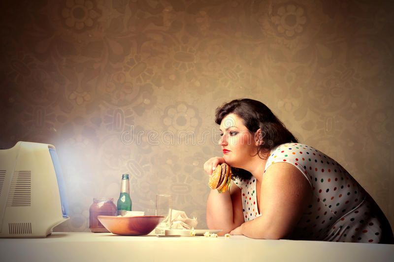 Junk food for dinner. Overweight woman eating in front of the television stock photography