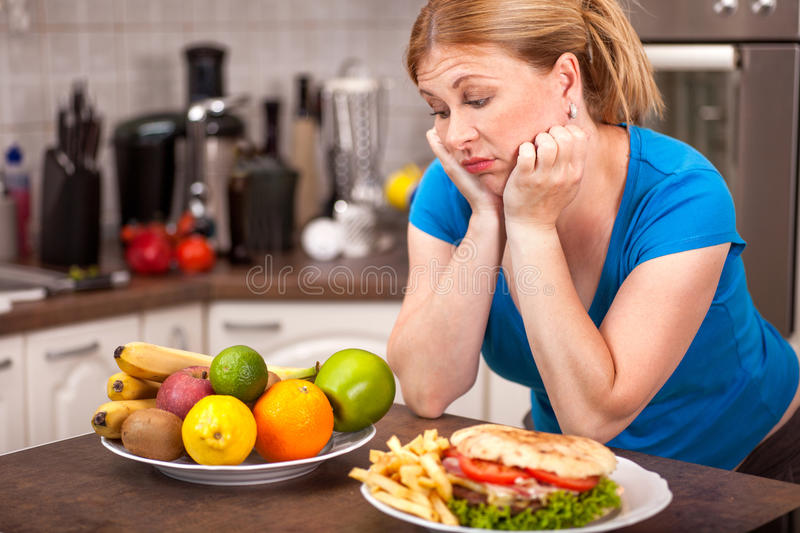 Junk food or healthy food,concept of pregnant woman on a diet. Portrait of pregnant woman with plate of junk food and a bowl of healthy food royalty free stock photo