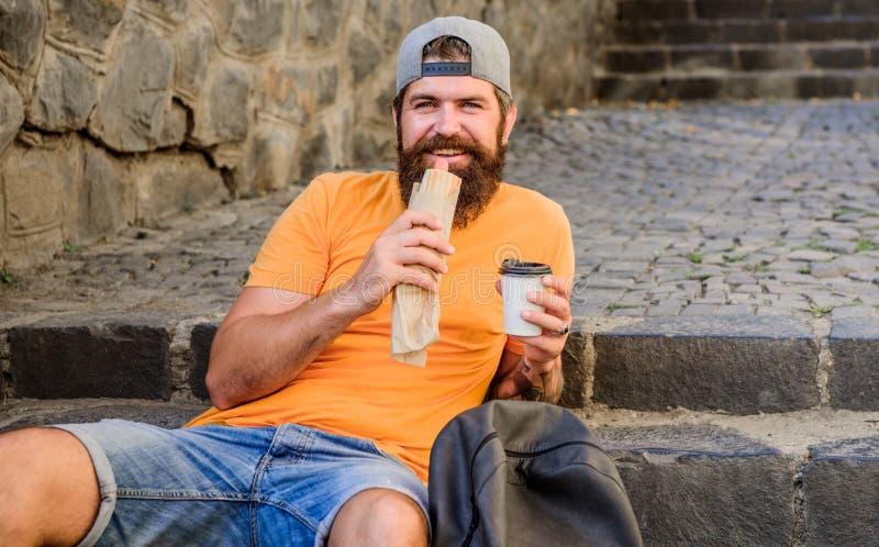 Junk Food Individuo que come el perrito caliente El hombre barbudo goza aprisa de la taza del bocado y de papel de la bebida Comi imagen de archivo