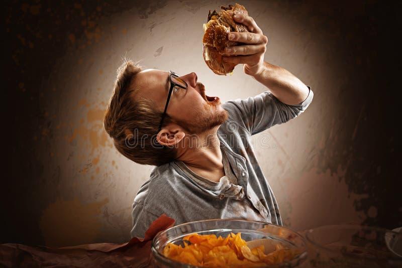 Junk Food. Man eats greasy fast food royalty free stock image