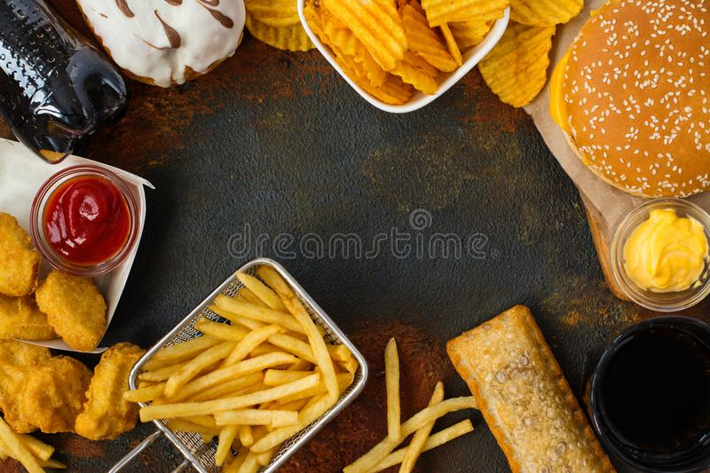 Assortment of fast food. Junk food on table. Fast carbs not good for health, heart and skin. Space for text stock photo