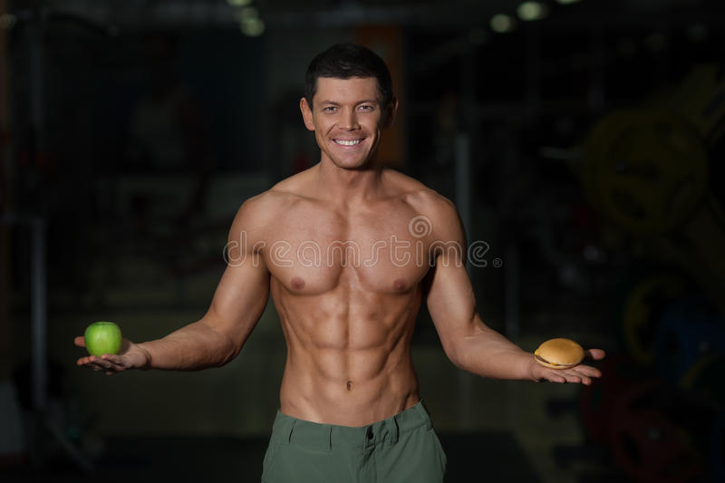 Junk food vs healthy diet concept. Sporty athlete with apple and hamburger in hands stock images