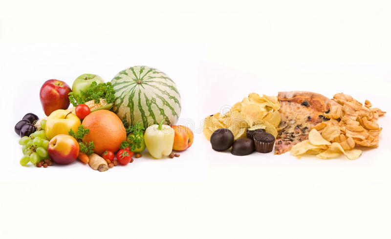 Junk Food VS Healthy Food. Fresh vegetables and fruits VS junk food stock photos