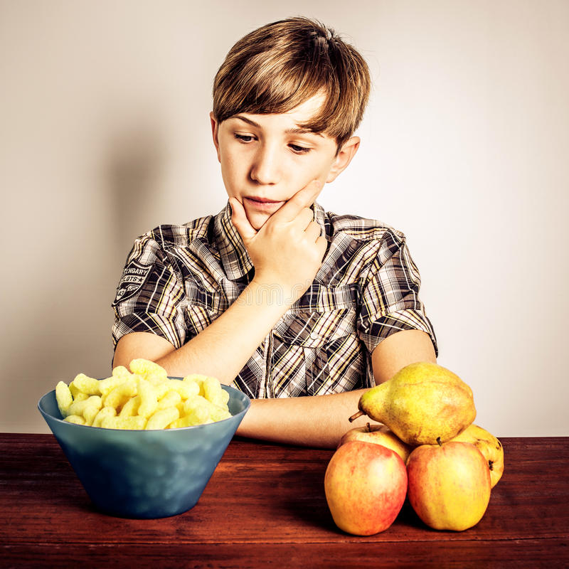 Junk food vs healty food. Boy who must make a decision junk food vs healty food royalty free stock photography