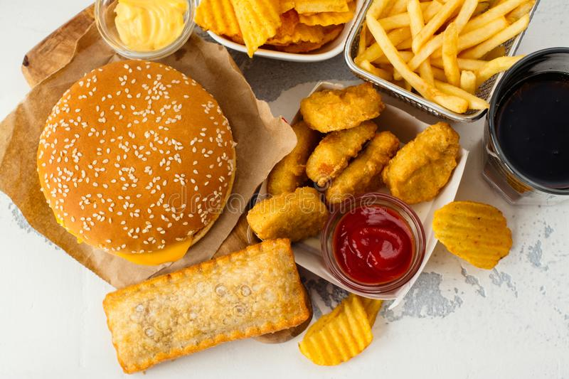 Assortment of fast food. Junk food on white table. Fast carbohydrates not good for health, heart and skin royalty free stock photo