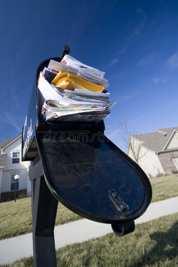 Junk mail. Mailbox full of junk mail with new houses and clear blue sky in the background stock image