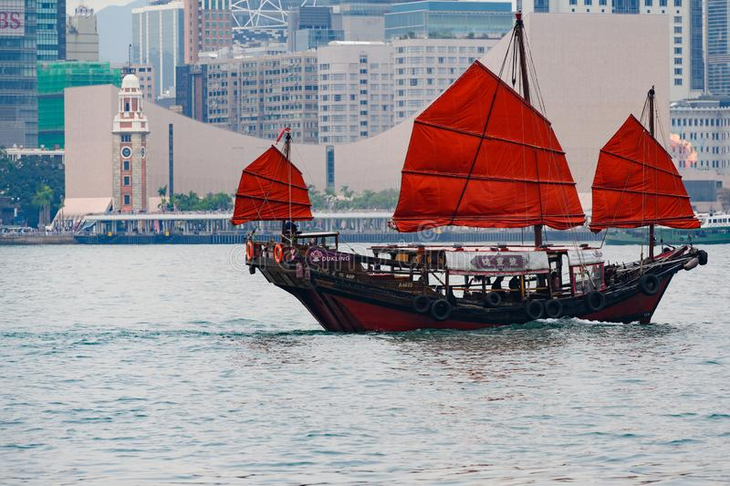 Junk with red sails crossing Victoria Harbour, Hong Kong stock image