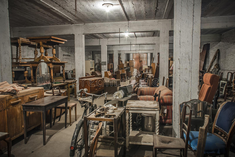 Junk Storage. A selection of antique furniture stored in an old warehouse stock photography
