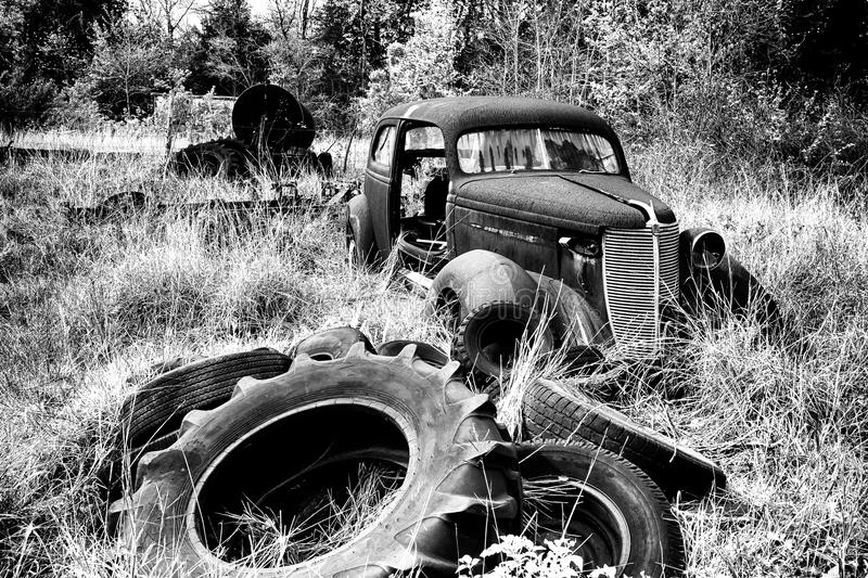 Junk Yard Car. Amid piles of used and discarded tires with vegetation slowly overgrowing everything royalty free stock photos