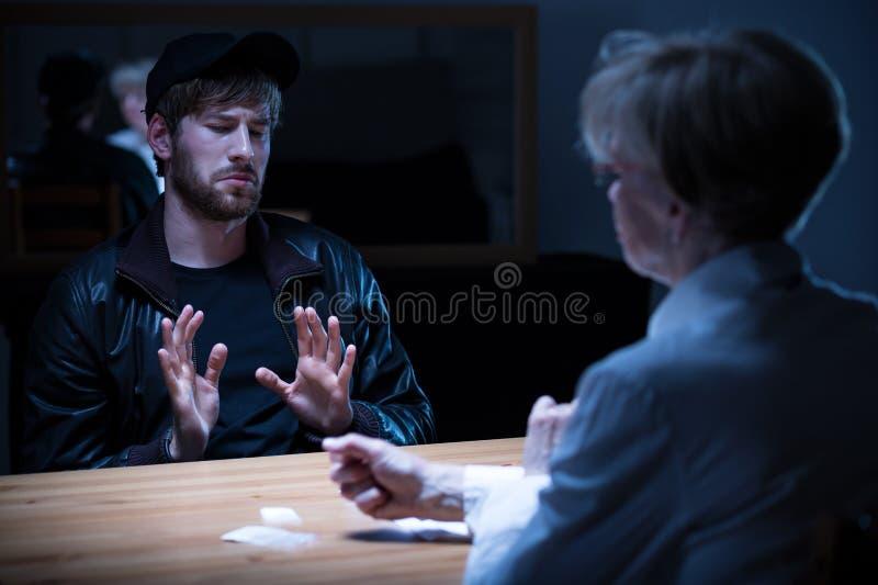 Junkie man interrogated by policewoman. Junkie men interrogated by policewoman in a dark room stock photo