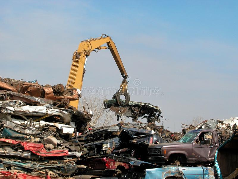 Junkyard crane with claw and crushed car stock photography