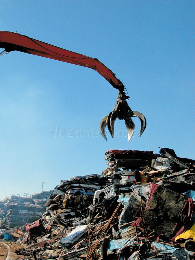 Junkyard crane with claw and crushed car stock images