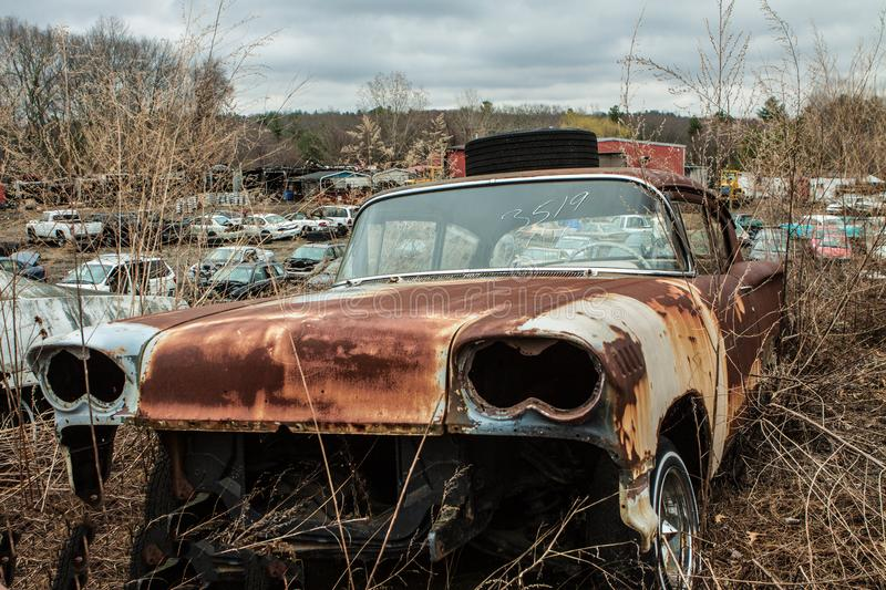 Junkyard rusty old abandoned car in car graveyard. Junkyard rusty old abandoned discarded car in car graveyard with other discarded cars in field on ominous royalty free stock image