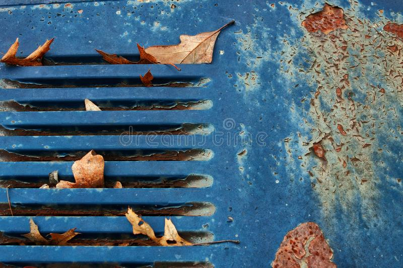Junkyard rusty old abandoned car with turquoise grille in car graveyard. Junkyard rusty old abandoned discarded car in car graveyard with turquoise rusty grille royalty free stock image