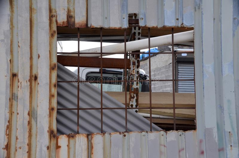 Junkyard Window. A window cut in corrugated metal wall shows the chaotic junkyard on the other side stock photo